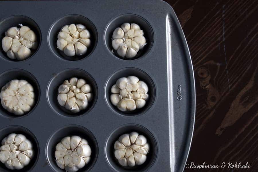Raw heads of garlic in a muffin pan