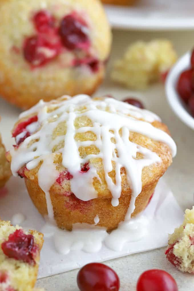 cranberry muffin topped with icing on a piece of parchment paper