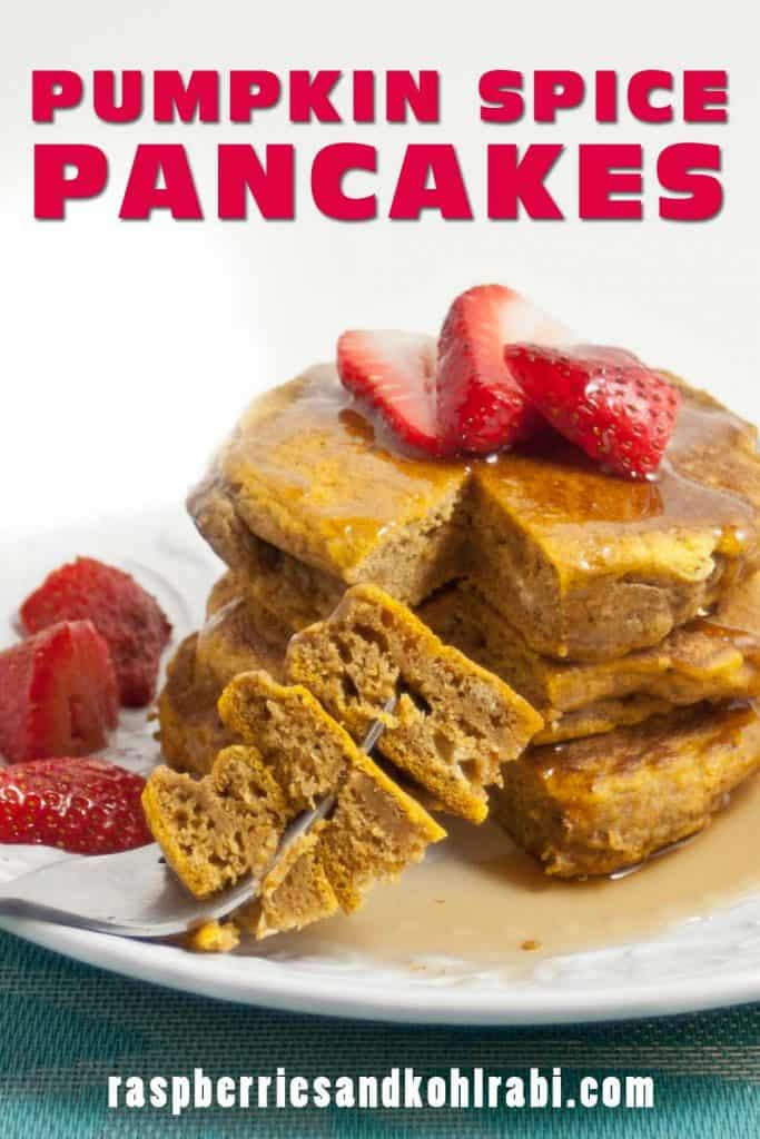 Stack of 3 pumpkin pancakes on a white plate topped with strawberries