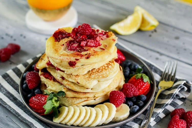 Pile of Raspberry Lemon Ricotta Pancakes topped with mixed berries
