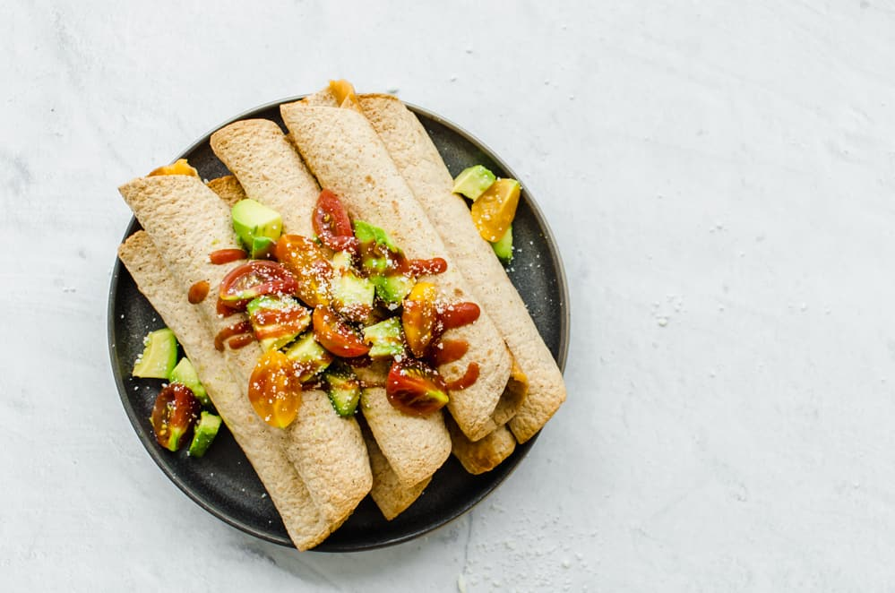 chicken and cheese taquitos on black plate