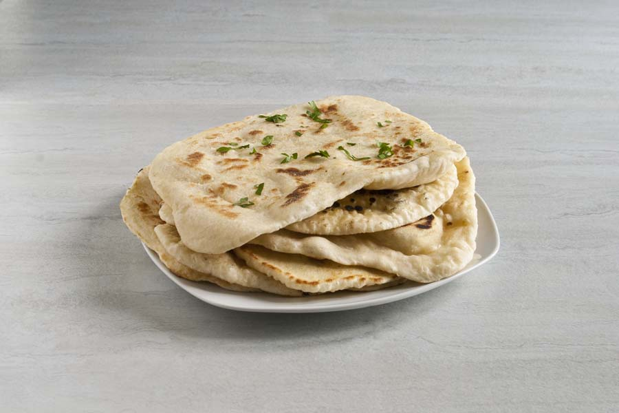 Pile of sourdough discard flatbread on a white plate