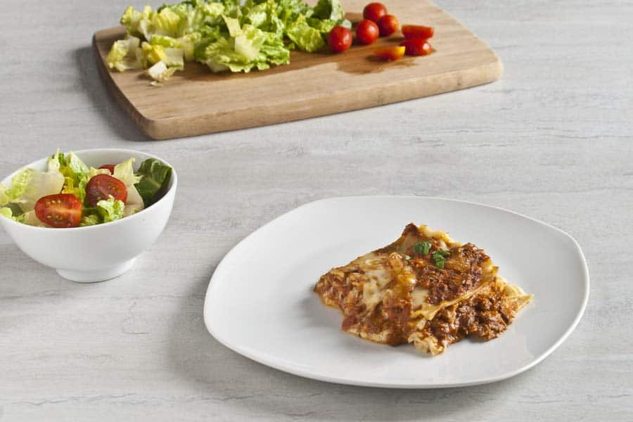 slice of four cheese lasagna on white plate with salad