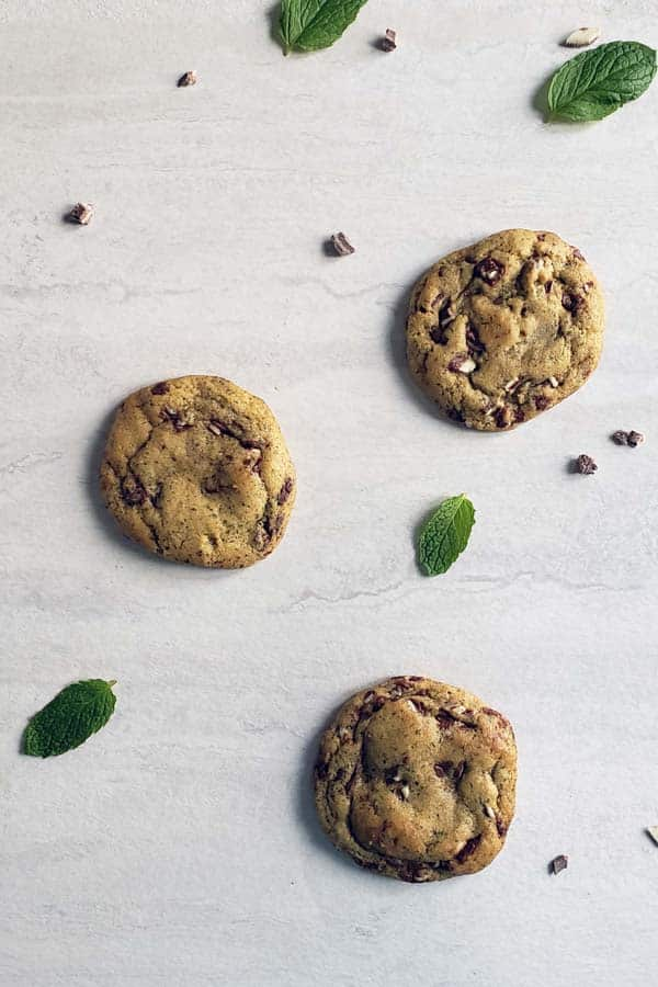 three fresh mint chocolate chip cookies on a white background