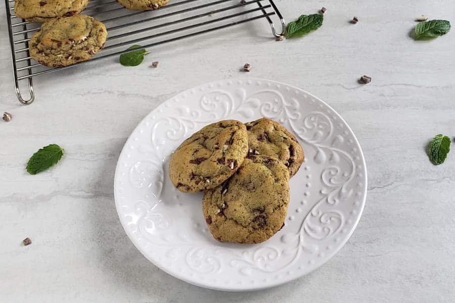 three fresh mint chocolate chip cookies on a white plate
