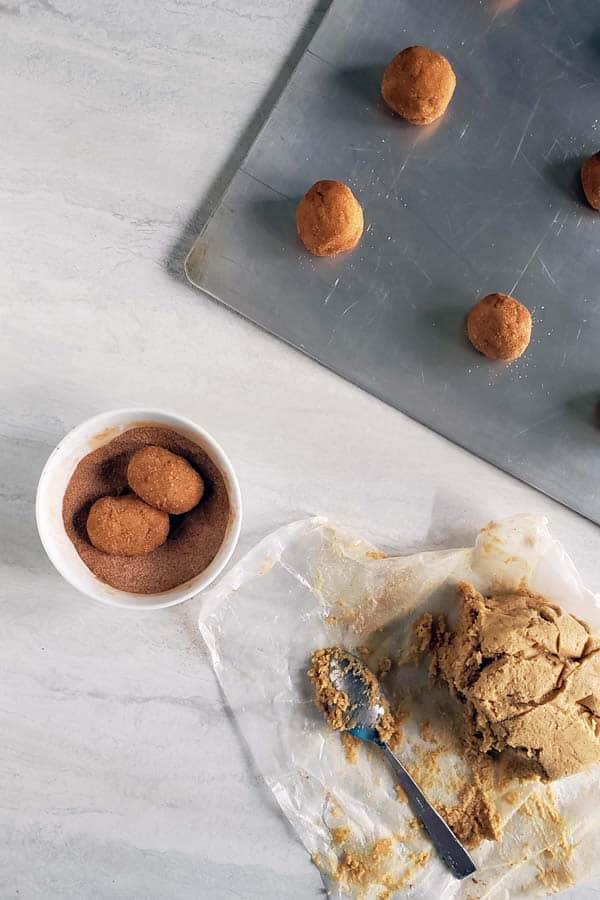 rolled sourdough snickerdoodle dough balls on baking sheet