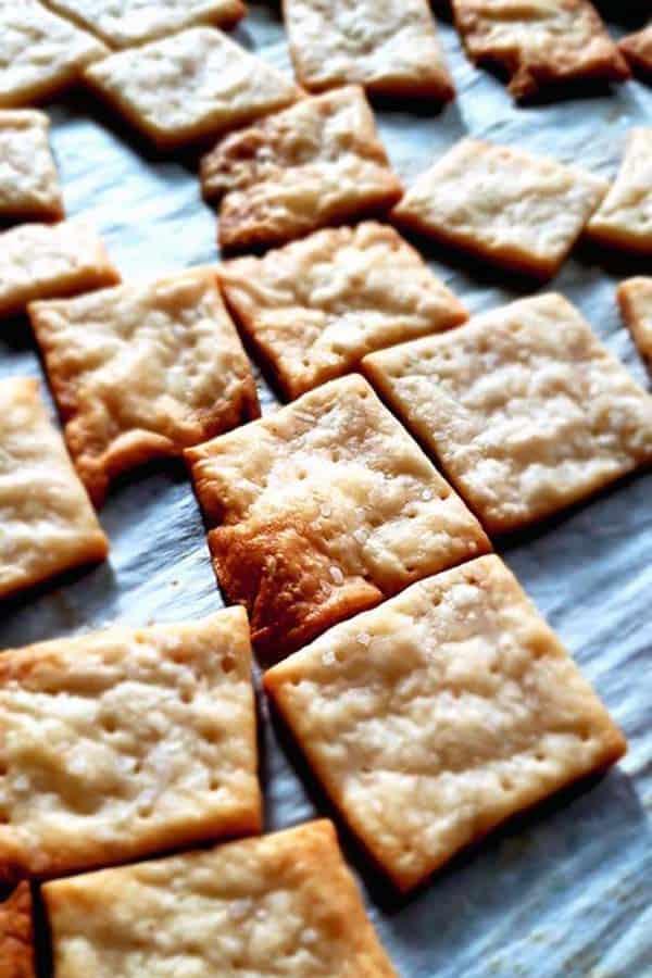close up of sourdough crackers on parchment paper