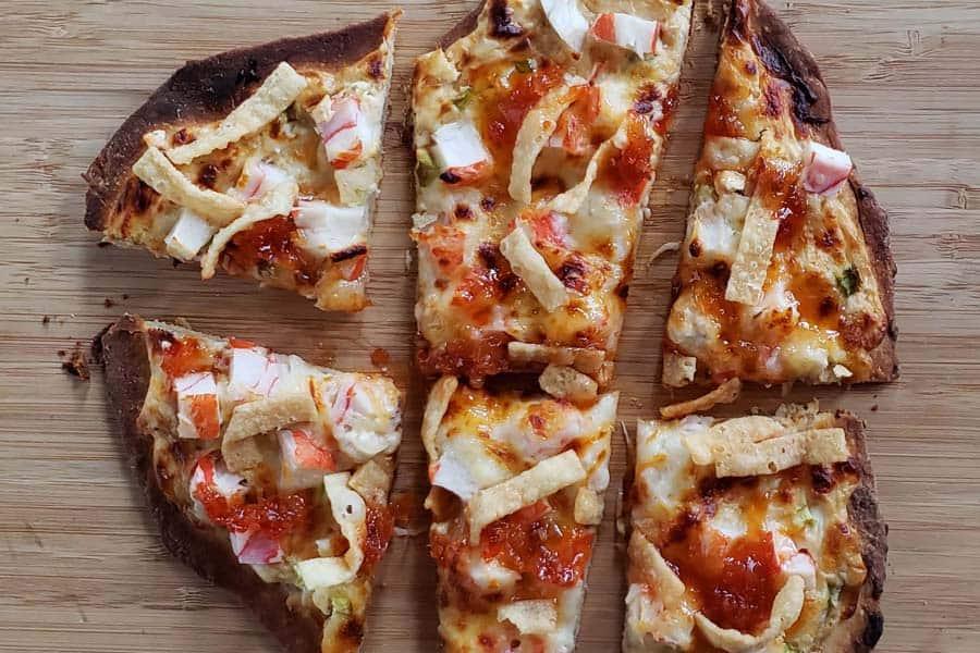 cut up crab rangoon pizza on cutting board