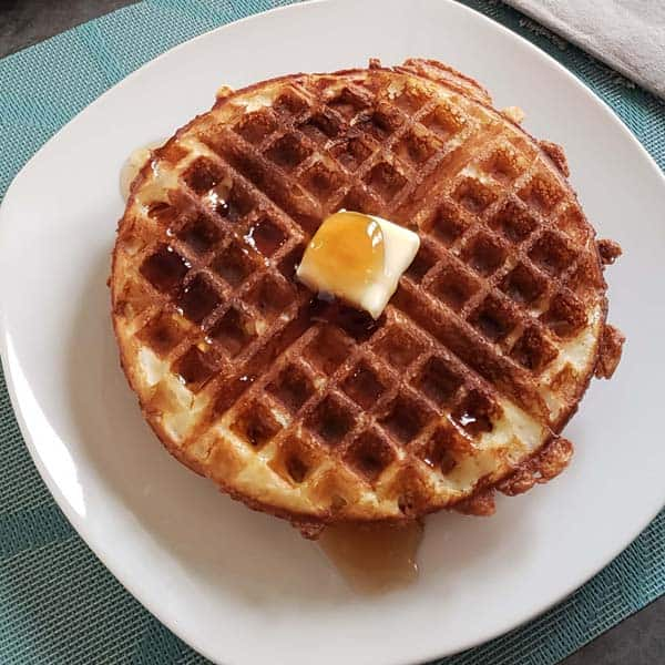 close-up of sourdough waffles on white plate with butter and syrup