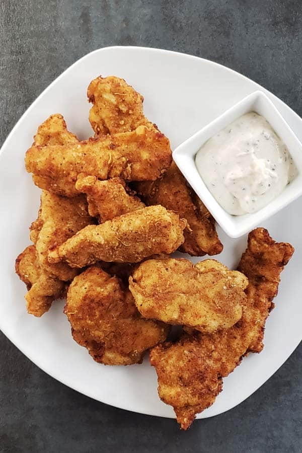 close up of sourdough chicken strips on a white plate with ranch dipping sauce