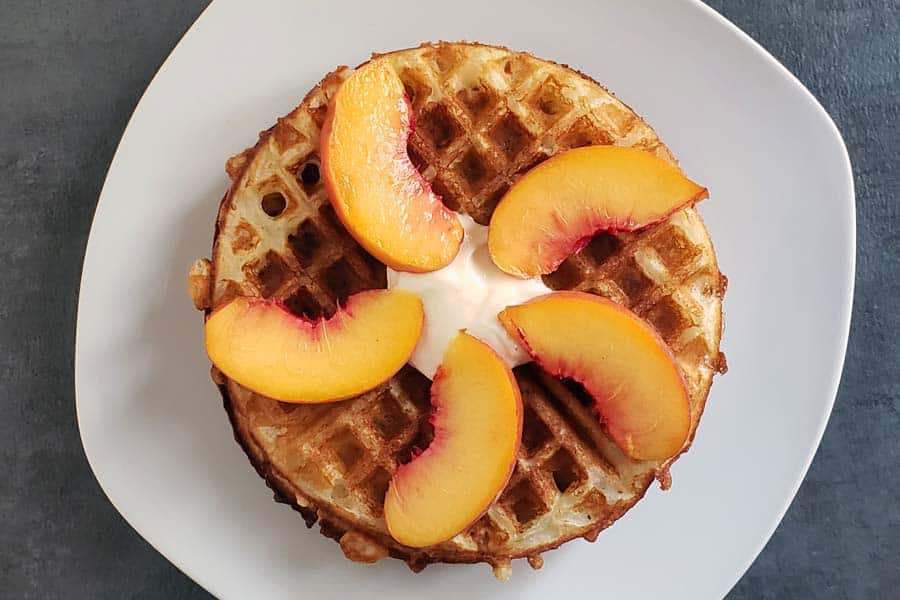 sourdough waffles on white plate topped with sliced peaches