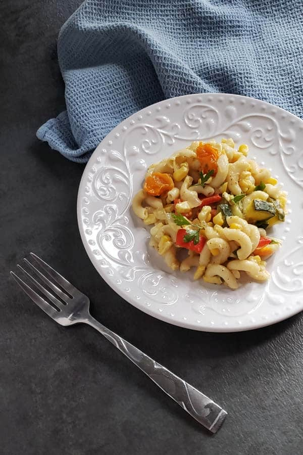 Tomatoes and Macaroni with Summer Vegetables on a white plate