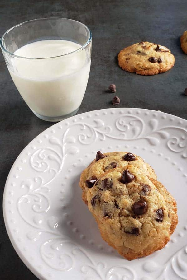 two amaretto chocolate chip cookies on a white plate