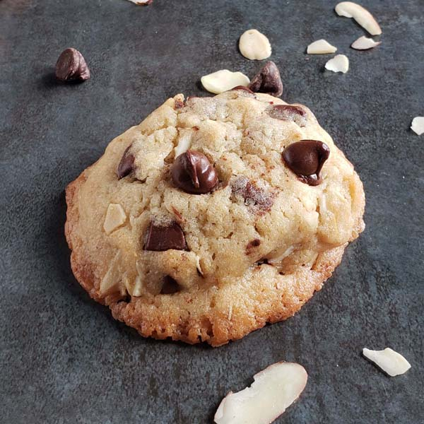 close up of amaretto chocolate chip cookie on dark background