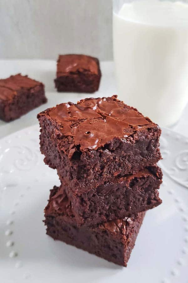 stack of three brownies made with sweetened condensed milk next to a glass of milk
