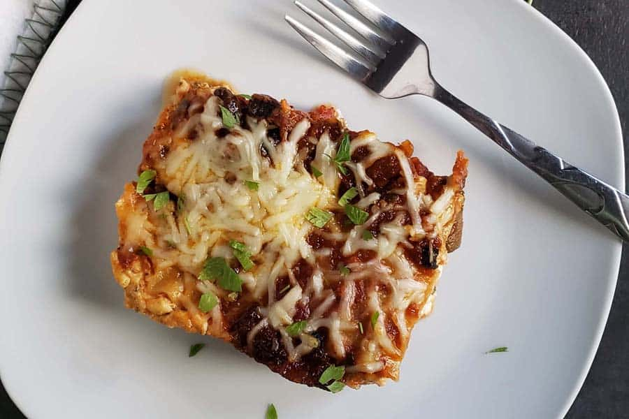 slice of four cheese lasagna on white plate with fork