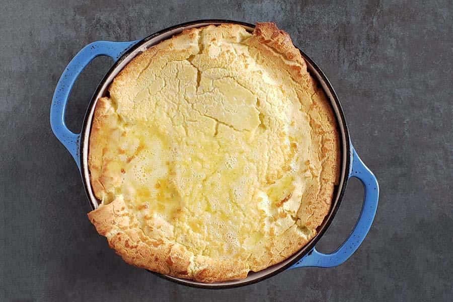fully risen sourdough dutch baby in blue dutch oven