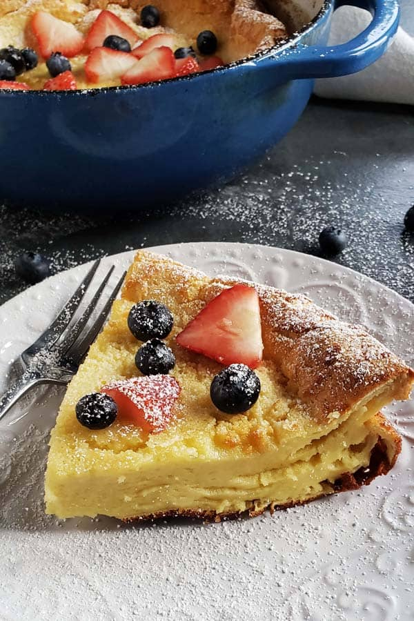 slice of sourdough dutch baby topped with powdered sugar, strawberries, and blueberries on a white plate