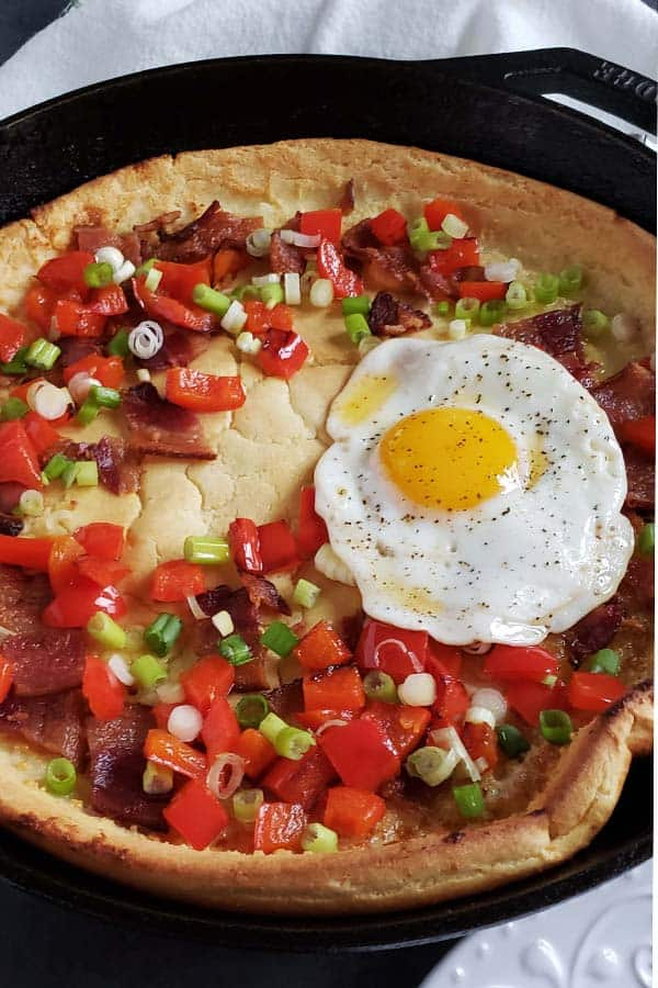 sourdough dutch baby in a cast iron skillet topped with bell peppers, green onions, bacon, and a fried egg