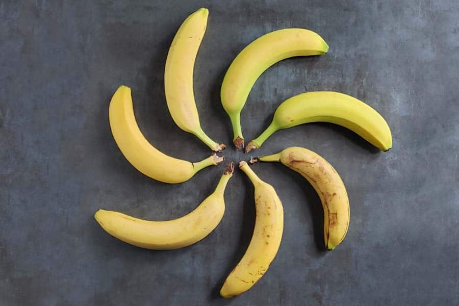 bananas at varying ripenesses on a dark background
