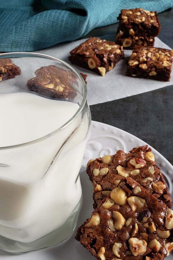 nutella brownies on a white plate with a glass of milk