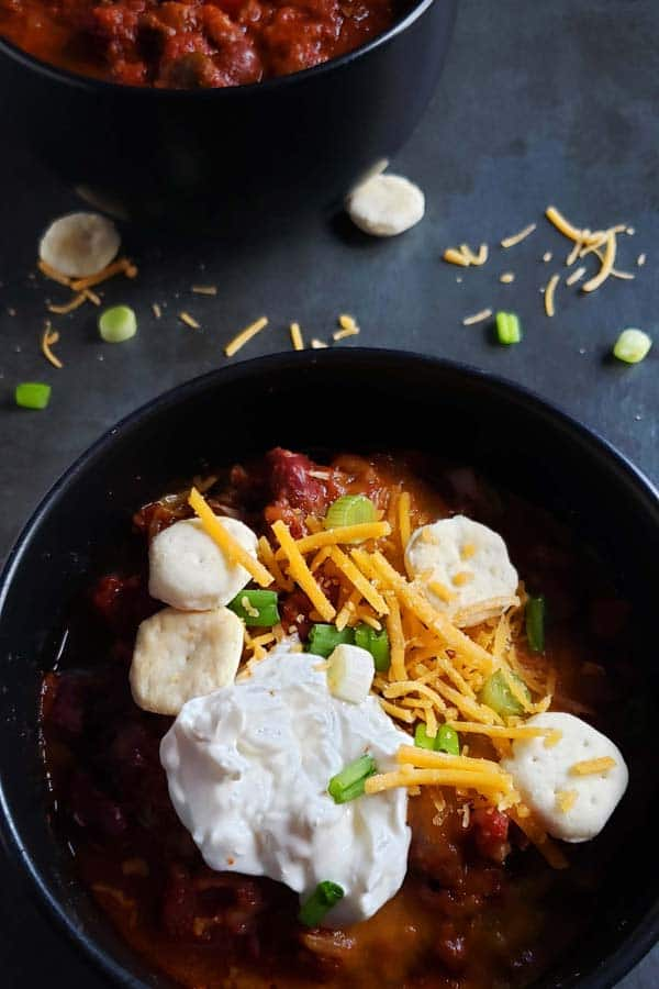 close up of chili in a black bowl topped with cheese, sour cream, green onions, and oyster crackers