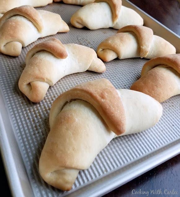 Six sourdough crescent rolls on a metal sheet pan
