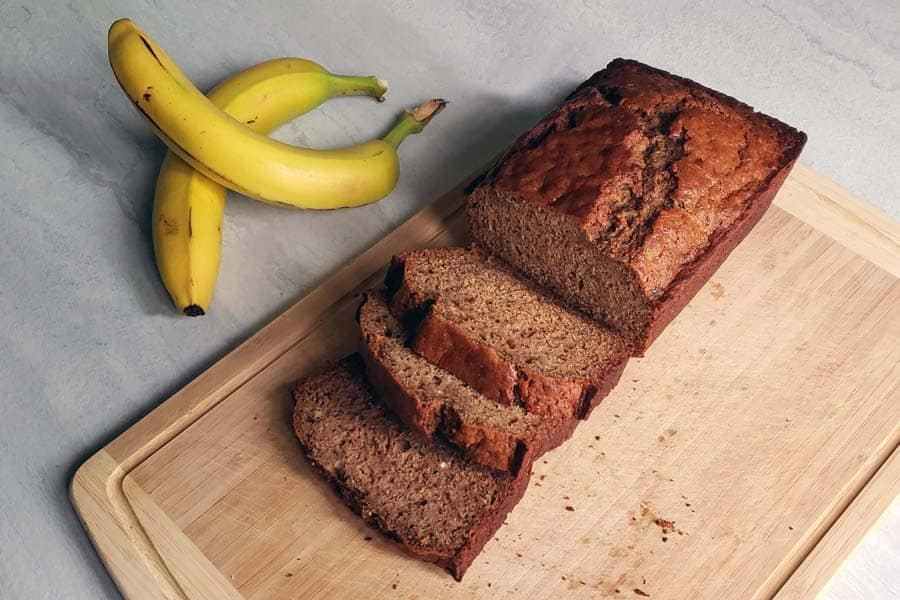 loaf of banana bread sliced on a wooden cutting board