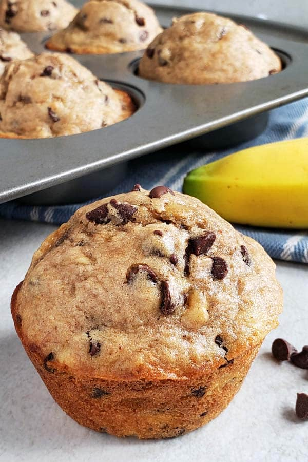close up of sourdough chocolate chip banana muffin on a white background