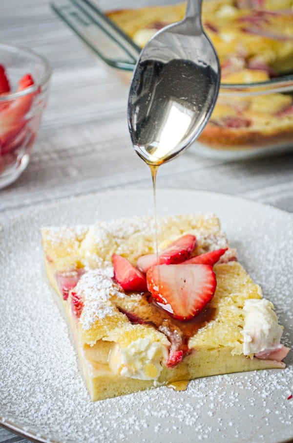 slice of sourdough pancake on a white plate topped with strawberries, powdered sugar, and syrup